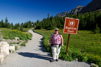hiker next to Highline Trail Trailhead sign