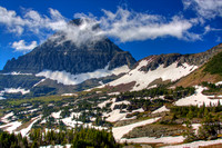 A whispy cloud drifts pasts Mount Reynolds - Glacier National Park