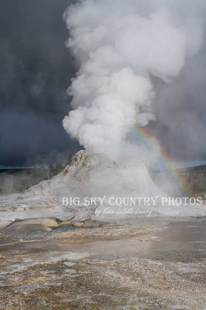 Castle Geyser performs against a storm dark sky with sunlight illuminating the water and steam of the eruption